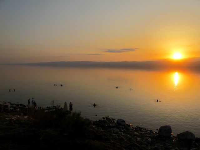 floating in-the-dead-sea-at-sunset-photo