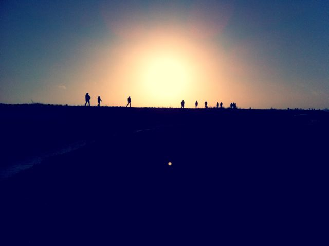 I captured this shot of people strolling along the dike against the background of a setting sun.